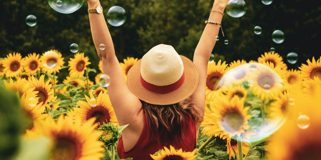 how to stay positive in difficult times. A woman with a hat surrounded by sunflowers