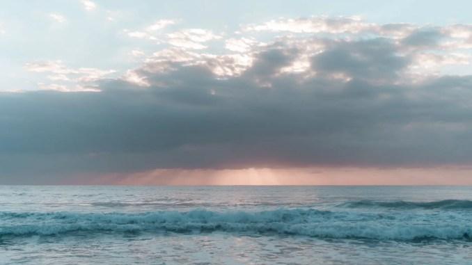 foamy ocean under cloudy sky at sunset