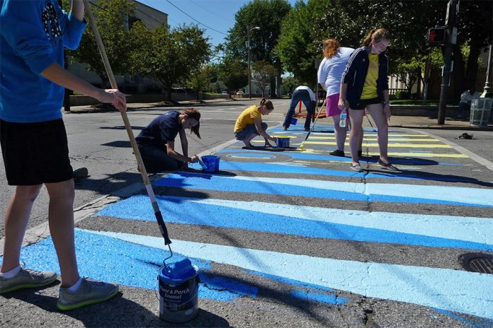 Volunteers paint colorful crosswalks along Fourth Street in SoBro.