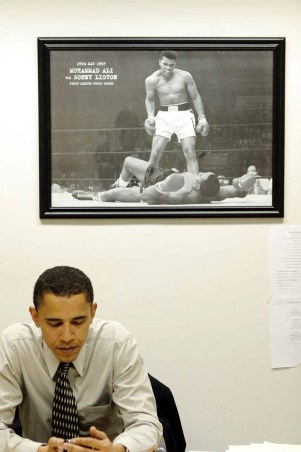 President Barack Obama sits in his private office in front of a photo of Muhammad Ali. (Courtesy The White House)