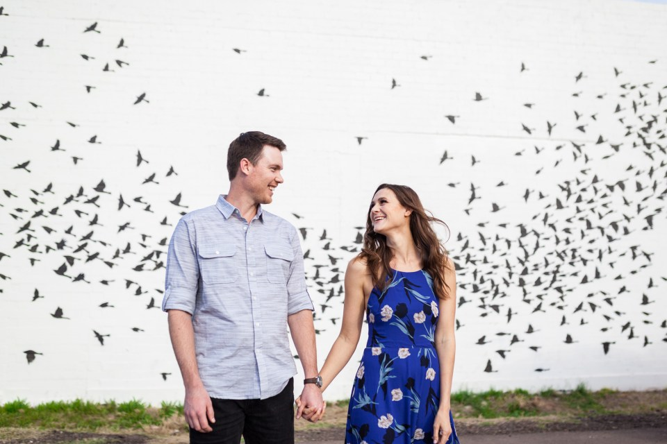 flying birds wall mural engagement photos in downtown phoenix arizona with long flowy blue dress
