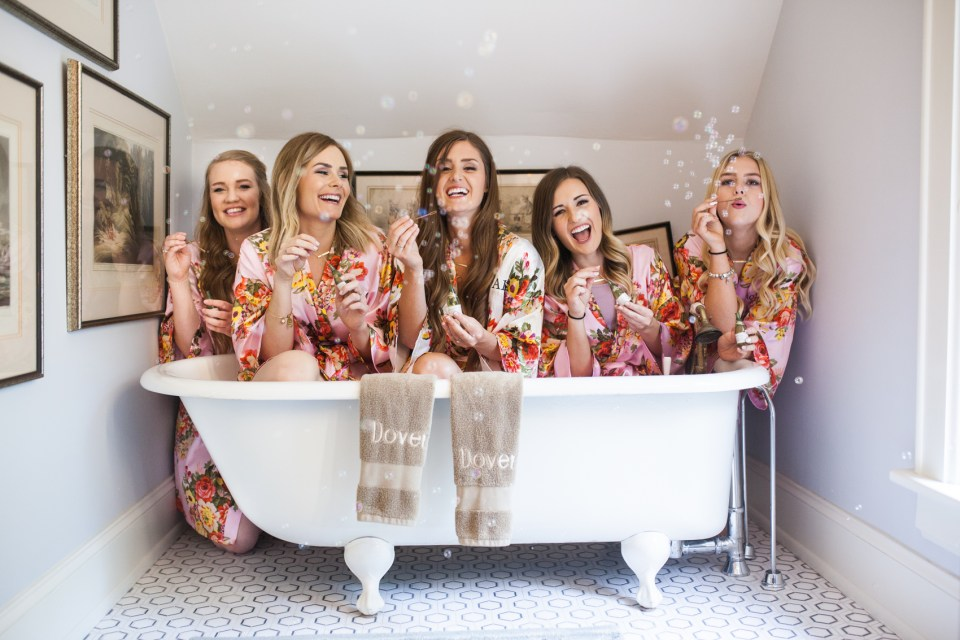 bridesmaids blowing bubbles in a claw foot bath tub