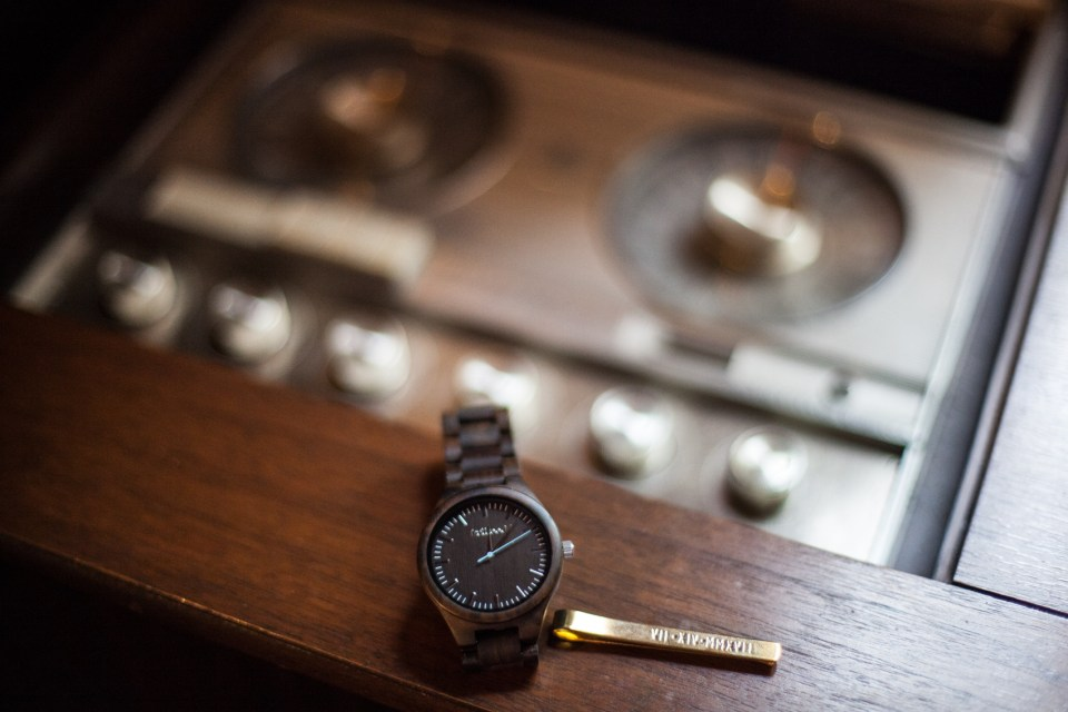 grooms watch and tie bar clip on top of vintage music player