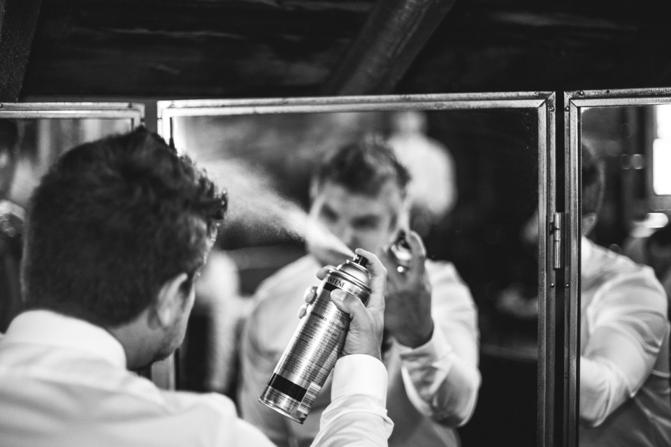 groom getting ready for wedding spraying hairspray in black and white