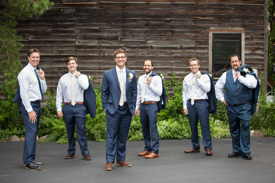 groom and groomsmen in blue suits and pink ties with jackets over shoulders
