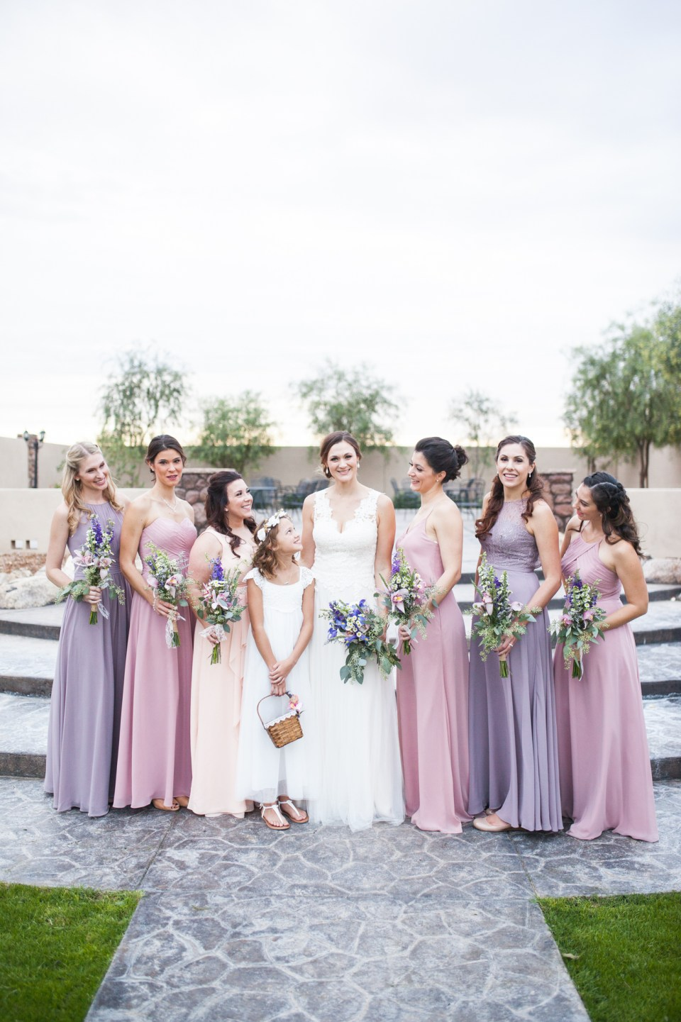 Bride with bridesmaids in pink and purple dresses