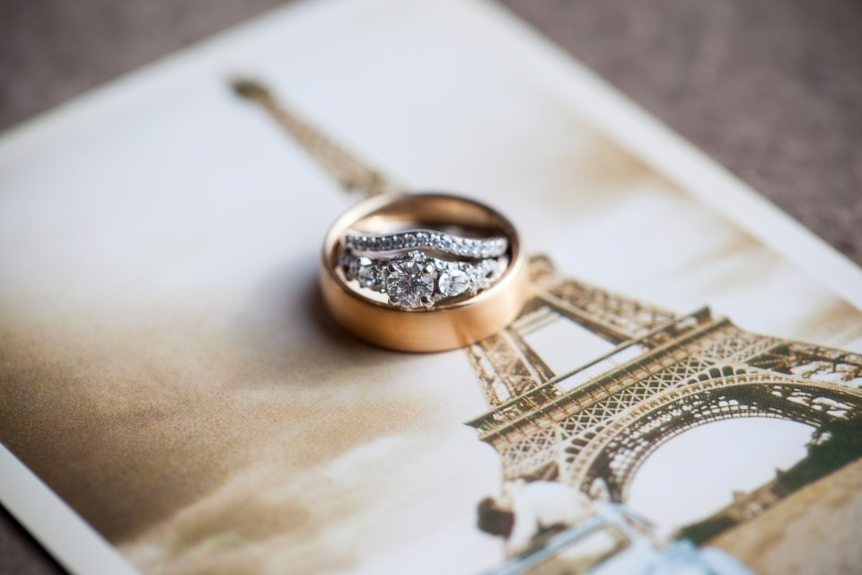 round diamond ring with decorative setting and copper mens wedding band on paris postcard