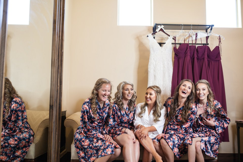 bride and her bridesmaids laughing with dresses in background