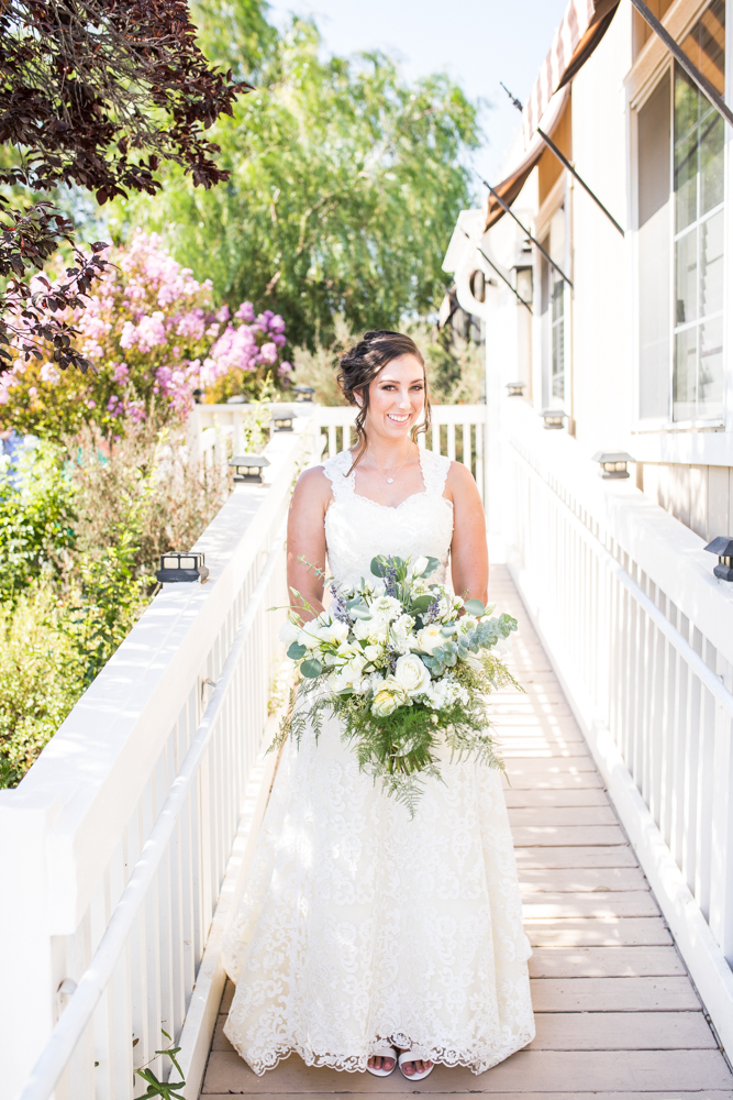 bride in lace wedding dress and large bridal bouquet with greenery and white flowers