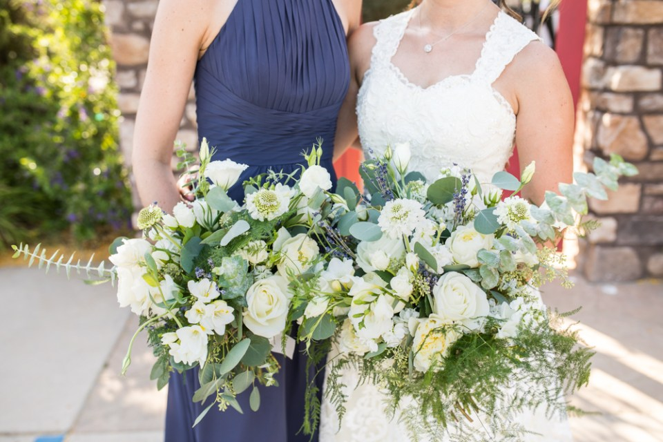 bride and bridesmaid with large bridal bouquet with greenery and white flowers