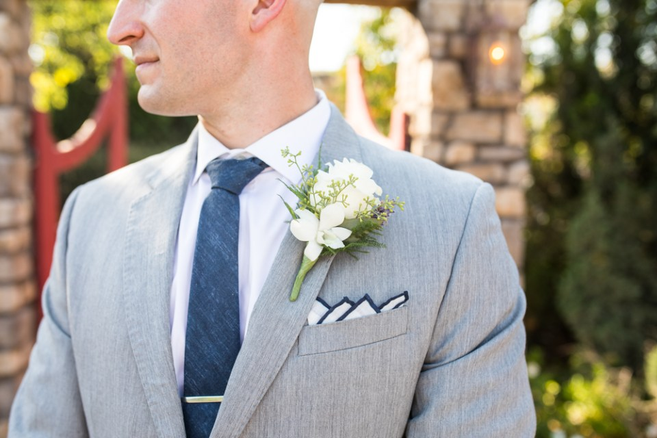groom in grey suit with navy blue tie and four peak fold pocket square