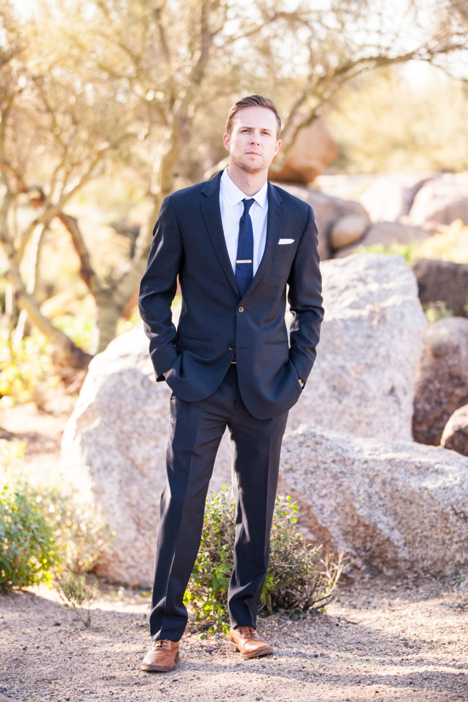 groom in black tux with navy blue tie