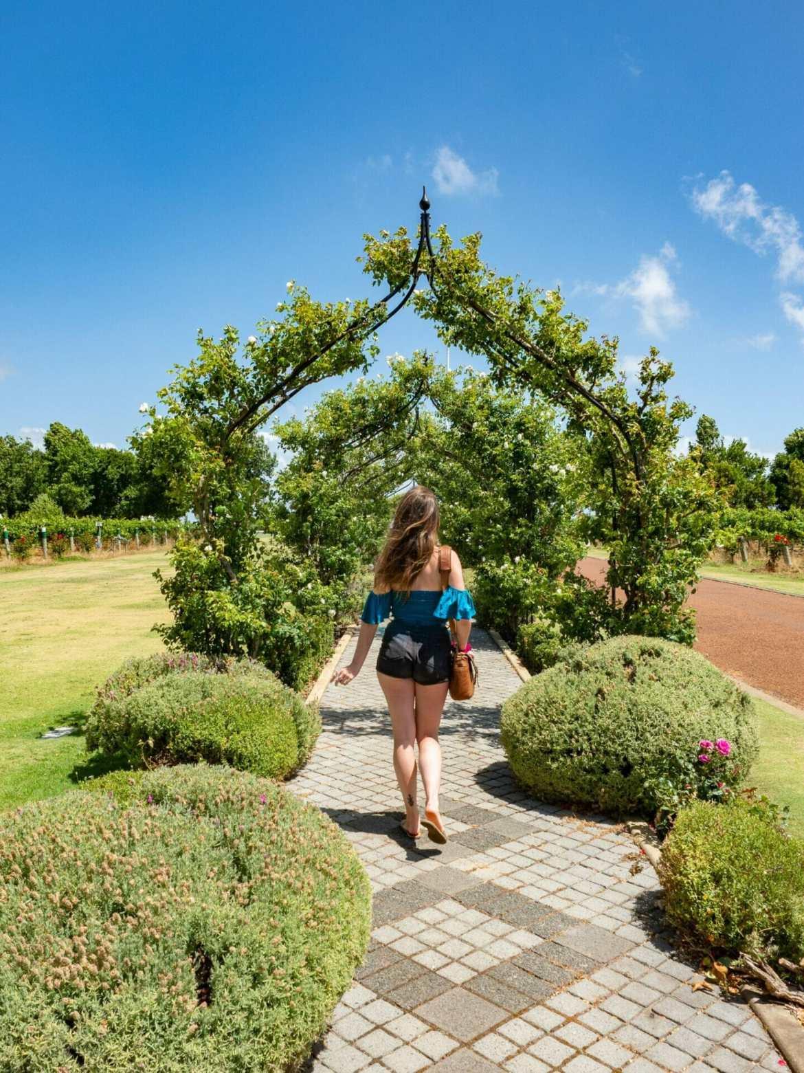 Woman walking in garden wine cellar door Margaret River