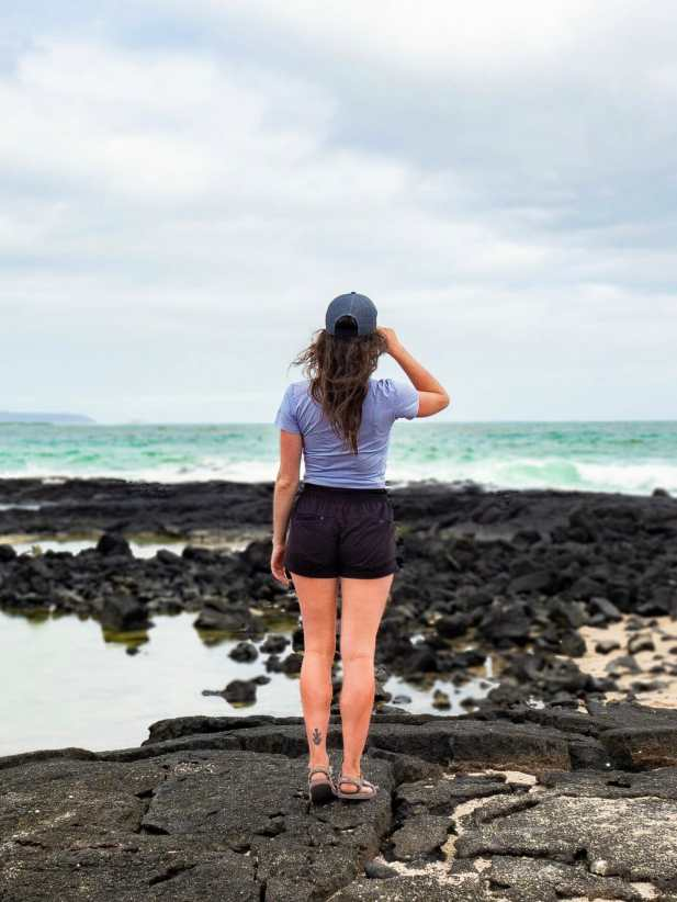 Girl standing on black volcanic rock Playa del Amor