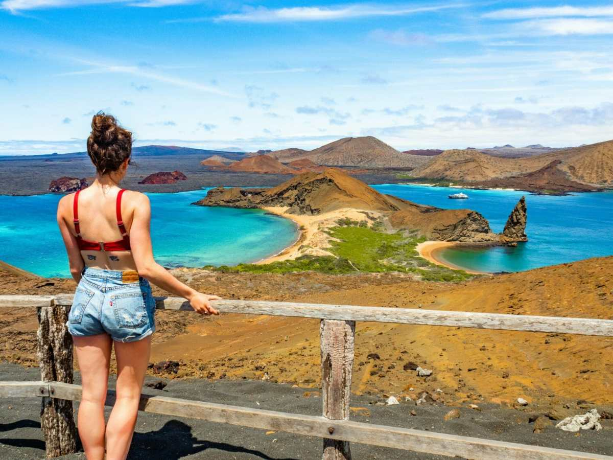 Girl looking at colourful beach and volcanos Isla Bartolomé Galápagos