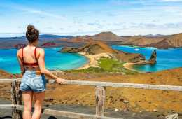 Girl looking at colourful beach and volcanos Isla Bartolomé Galápagos