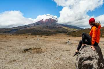 Girl on rock in front of Cotopaxi Volcano