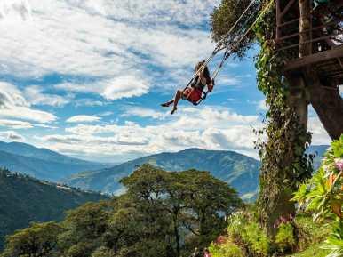 Girl swinging over mountains Casa del Arbol in Baños
