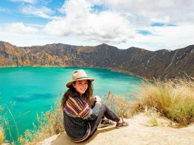 Girl in colourful sweater at Laguna Quilotoa turquoise lake Ecuador