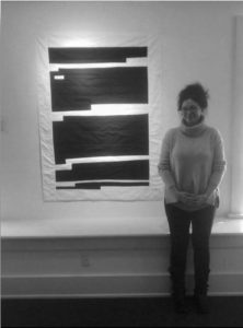 """Brooke Blackmon Bryan stands before her quilted textile """"Harm to Ongoing Matter/Redacted No 1"""" in the Exhibit """"Antioch Works"""" at the Herndon Gallery in Yellow Springs, Ohio, 2019."""