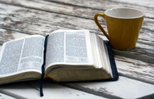 Bible and coffee cup on a weathered picnic table