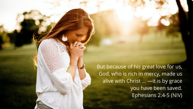 woman praying in a park at sunrise with quotation of Ephesians 2:4-5, NIV