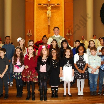 Parish children stand with Msgr. Gigantiello in front of the altar. - Brooklyn Archive