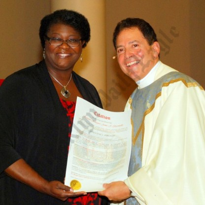 State Sen. Roxanne Persaud presents Msgr. Gigantiello with a citation. - Brooklyn Archive