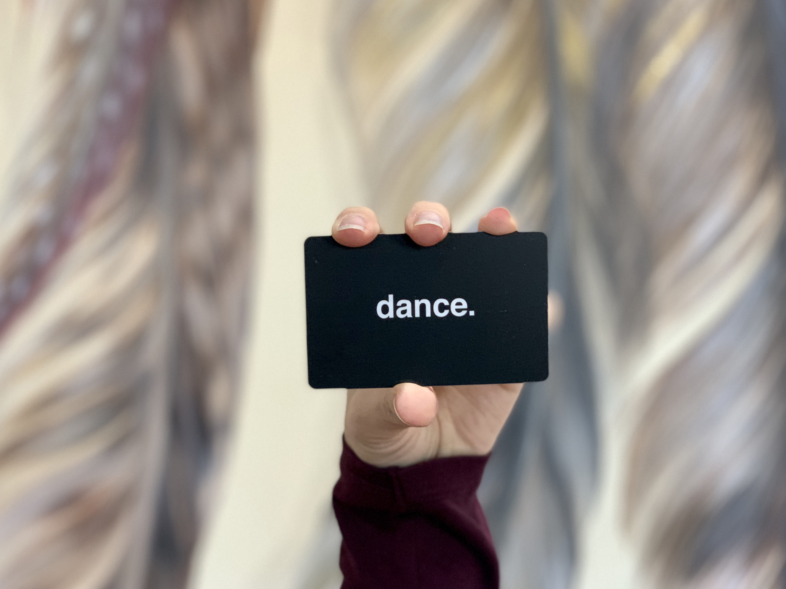 Gift card held in woman's hand with blurred background