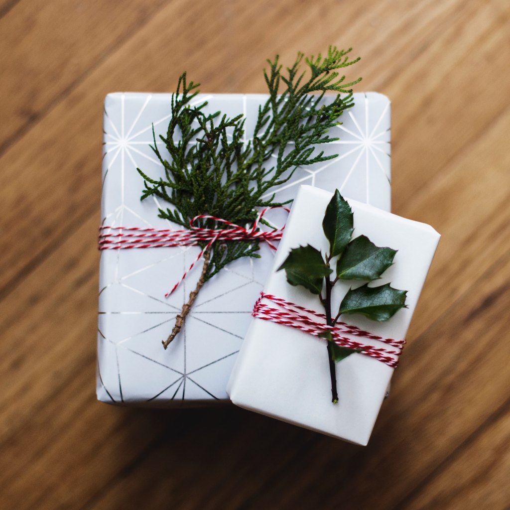 A picture of presents with pine and holly stems tied to the top