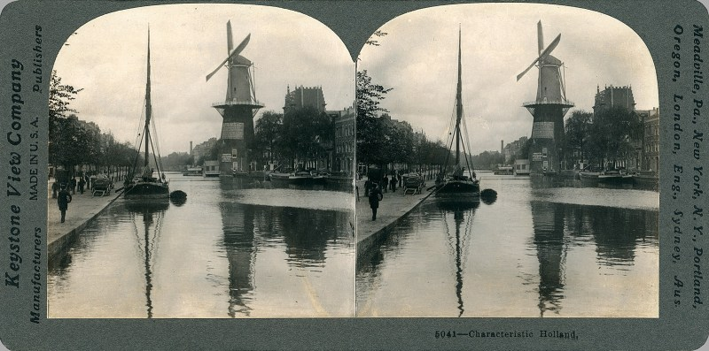 A view of a canal, with a boat moored on the left bank, and a windmill on the right bank, somewhere in The Netherlands.