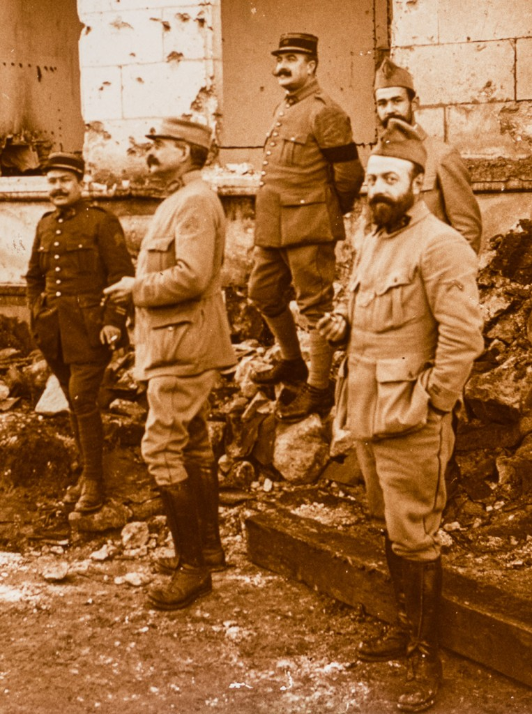 Three of the soldiers directly address the camera; two do not. All three whose hands are visible are smoking cigarettes. Smoking was almost universal in the French Army during the Great War.
