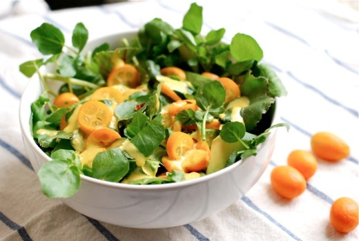 A colorful watercress and avocado salad with beet greens and kumquat slices, tossed with a punchy kumquat dressing.