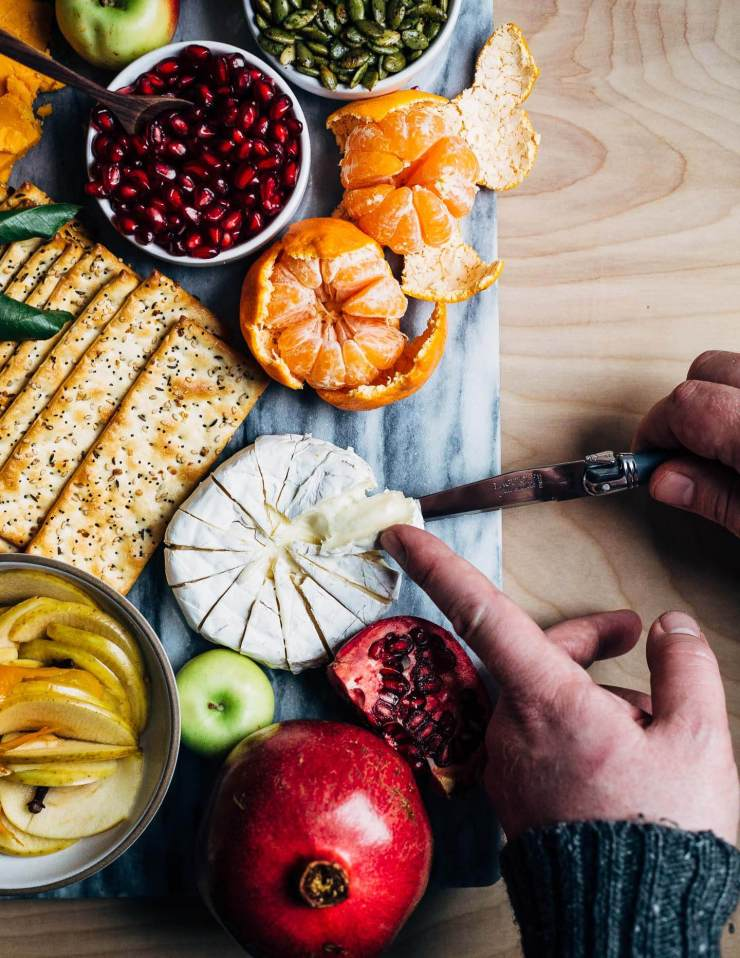 A modern holiday cheese board with red cheddar and brie-style cheeses, winter fruit, and sweet and sour quick-pickled apples.