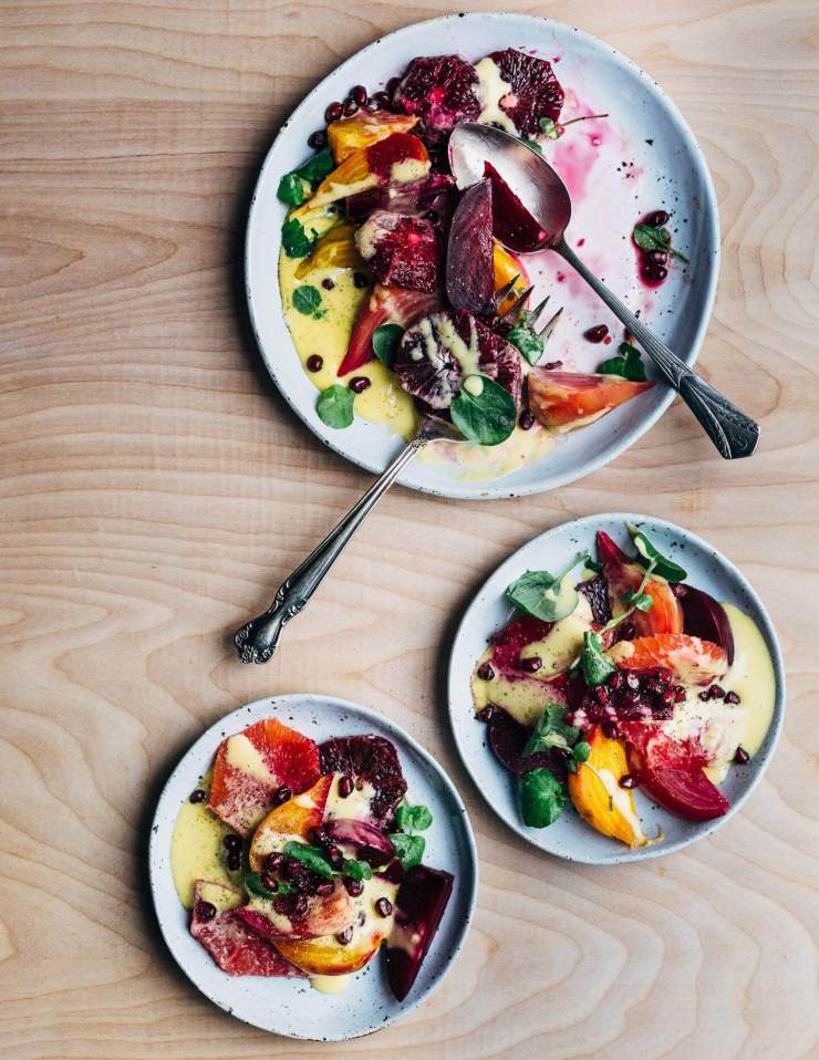 A jewel-toned winter orange and beet salad with layers of Cara Cara and blood oranges, grapefruit segments, red, yellow and chioggia beets, and a creamy homemade grapefruit aioli.