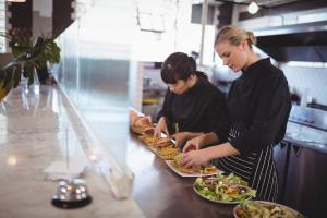 Young female chefs preparing fresh food at cafeteria