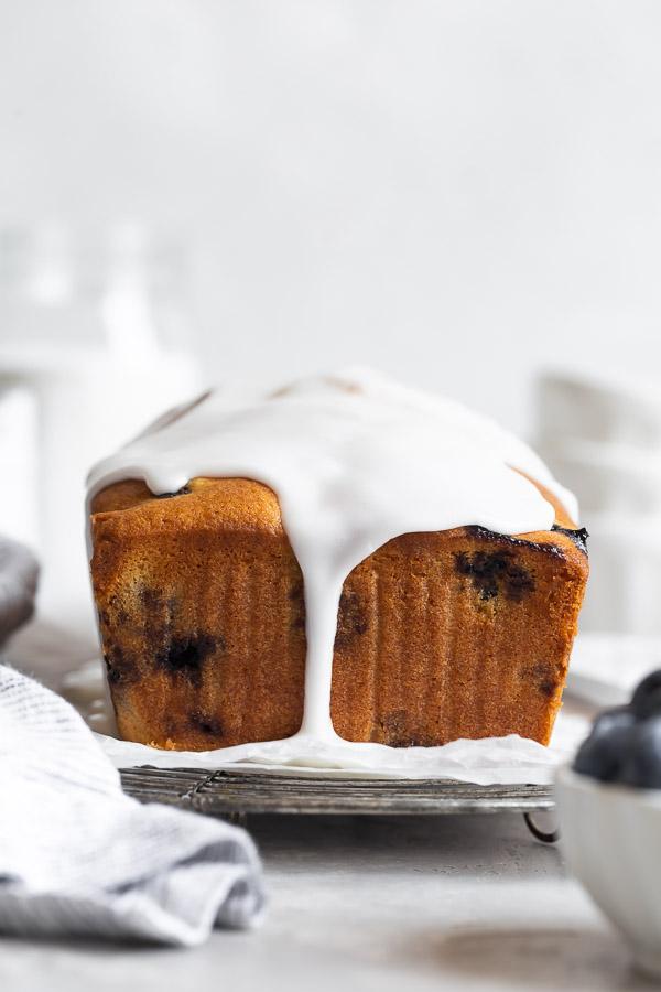 glaze dripping off of lemon blueberry cake