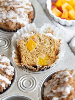 cross section of peach streusel muffin in muffin tin