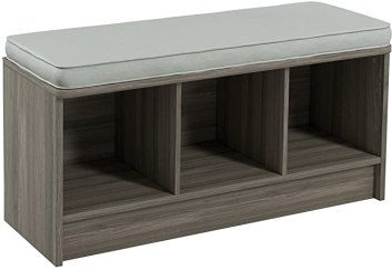 A gray storage bench with a cusion and 3 cubes to place things in.