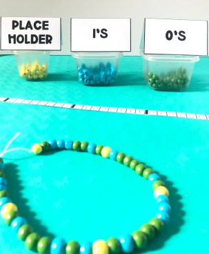 A blue, green, and yellow beaded necklace on a green background with cups labeled place holder, 1's, and 0's for teaching binary.