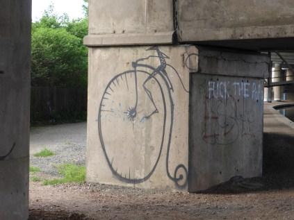 Oldbury, Tat Bank: several graffiti drawings on monkeys on penny farthings. OK.