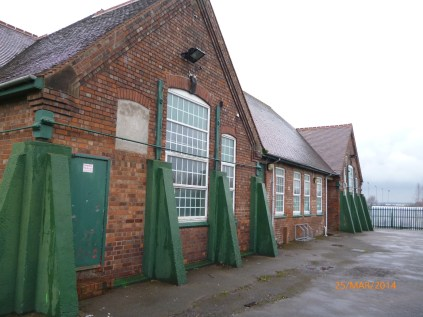 The former school stands at the foot of the playground of the current one. Image courtesy David Evans.