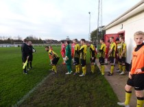 A sunlit, freezing day and the players take to the field. Hollbeach in yellow and black shirts