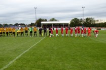 Customary handshake overture to today's match, with the Wood in bright red strip.