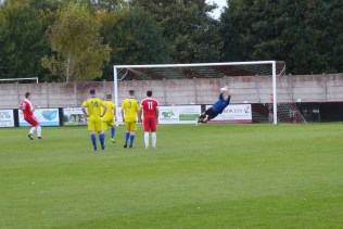 A thunderous penalty kick well defended by outstretched Sphinx goalkeeper. Super soccer