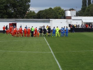 Walsall Wood welcome Whitchurch ( in blue) and their throng of excellent supporters.