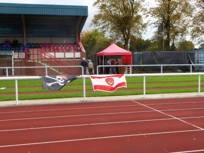 Nuneaton's grass football ground is encircled by a running track - not greyhounds, though! This made for distant spectating, while the Wood's banners proclaimed a presence.