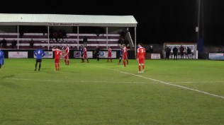 Players brace themselves to receive a long ball from Wednesfield goalkeeper, who was to have a busy night, thus keeping the cold at bay.