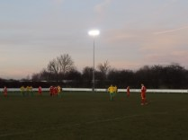 Second half, played under floodlights. A Virgin dashes past in the near distance