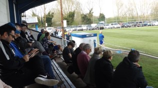 A goodly crowd of eager supporters sat sitting in the stand, while others clutched the rails.